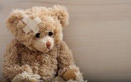 Плюшевый медвежонок с повязкой на деревянном поле стоковая фотография rf