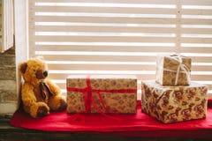 Плюшевый медвежонок, с подарками на силле окна Стоковая Фотография