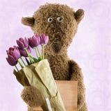 Плюшевый медвежонок с цветками стоковые изображения