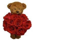 Плюшевый мишка держа букет красных роз на день Valentine's стоковые изображения rf