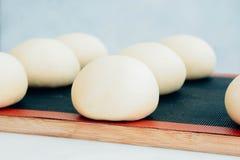Плюшки дрожжей перед печь, ложь на листе выпечки с бумагой выпечки Круглые плюшки смазаны с яичком Варочный процесс Стоковое Изображение