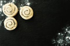Плюшки с сахаром и маковыми семененами, тестом лежа на черной каменной разделочной доске взбрызнутой с мукой стоковая фотография rf