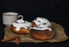 Плюшки с циннамоном и кофе на пергаментной бумаге и темной предпосылке Стоковое Фото
