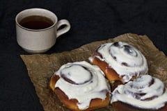Плюшки с циннамоном и кофе на пергаментной бумаге и темной предпосылке Стоковые Фото