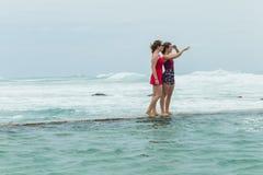 Пляж девушек стоя приливный океан бассейна Стоковые Фото