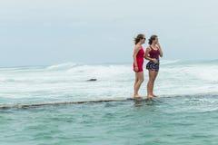 Пляж девушек стоя приливный океан бассейна Стоковые Изображения RF