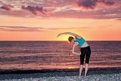 пляж делая утро девушки тренировок рассвет Взгляд от b Стоковые Изображения RF