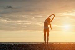 пляж делая утро девушки тренировок рассвет задний взгляд Стоковая Фотография