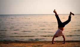 пляж делая человека handstand Стоковые Фото