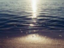Пляж и море песка развевают в свете захода солнца, запачканной абстрактной предпосылке лета стоковая фотография rf