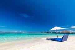 пляж красивейший Sunbeds с зонтиком на песчаном пляже около моря Стоковая Фотография