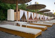 Пляж к морю с шезлонгами и сложенными зонтиками стоковое изображение rf