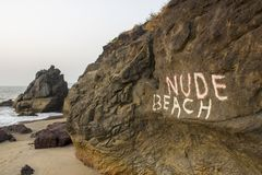 Пляж надписи обнаженный на утесе на предпосылке песчаного пляжа и моря стоковое изображение rf