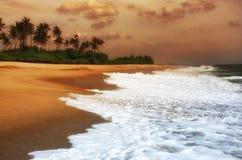 пляж над заходом солнца тропическим Стоковое Изображение