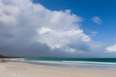 Пляж океана белого песка красивый под бурными облаками и голубым небом Стоковая Фотография RF