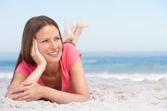 пляж ослабляя песочных детенышей женщины стоковые фото