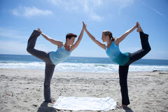 пляж практикуя йогу 2 женщин Стоковые Изображения