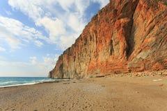 Пляж рая при большой красный утес спуская к морю Стоковая Фотография