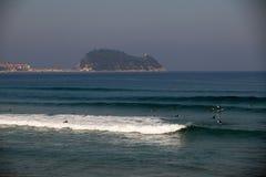 Пляж серфера Zarautz при люди занимаясь серфингом перед Getaria стоковые изображения