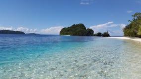 Пляж с белым песком с голубой водой tosca внутри рядом с зеленым островом леса Стоковое Изображение