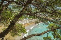 Пляж с зонтиками и loungers солнца Взгляд от горы через деревья Budva Черногория 9-ое сентября 2017 стоковое изображение