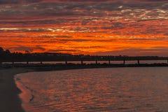 Пляж с красным небом на заходе солнца Стоковая Фотография RF