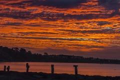 Пляж с красным небом на заходе солнца Стоковые Фотографии RF
