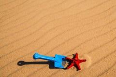 Пляж с ребенк забавляется лопаткоулавливатель, ведро и звезда Красного Моря Стоковое фото RF