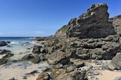 Пляж с свисанием утеса стоковое фото