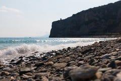 Пляж с скалой в предпосылке Стоковые Фото