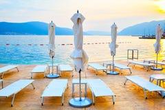 Пляж с deckchairs и зонтиками Стоковое Фото