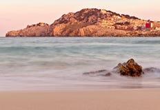 Пляж Cala Agulla на заходе солнца, с холмом и городком плюс скалистый передний план, mallorca, Испания стоковое изображение
