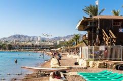 Пляж Eilat с людьми и посадки самолета на предпосылке городских белых зданий и m Стоковая Фотография RF