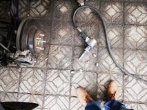 Пневматический ключ с гайками автошины автомобиля на конкретном пола автомобиле в сторону поднимает подъем и часть домкратом зарж стоковые изображения rf