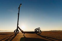 Пните самокат на следе асфальта идущем, под солнечным светом на солнечном летнем дне Стоковое Изображение