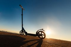 Пните самокат на следе асфальта идущем, под солнечным светом на солнечном летнем дне Стоковая Фотография
