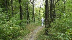 Побегите молодой человек в зеленом лесе сток-видео