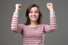 Победитель женщины поднимая оружия, обхватывая кулаки, крича с утехой стоковые фото