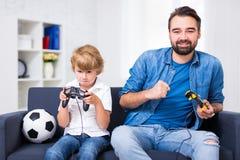 Победитель и проигравший - отец и сын при gamepads играя видео ga Стоковое Изображение RF