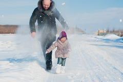 Побежали маленькая девочка и папа, который и игра с снегом, образ жизни, зимние отдыхи стоковые изображения