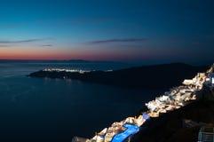 Побеленные дома с взглядом на море и Oia во время захода солнца внутри i Стоковое Изображение