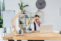 побеспокоенная коммерсантка сидя в офисе на ее столе, смотрящ экран компьтер-книжки и говорить стоковые фото