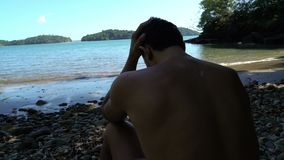 Побеспокоенный человек морем Молодой человек сидя на пляже, смотря потревожился Он хватает его голову сток-видео