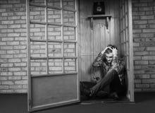 Побеспокоенный человек сидя на поле переговорной будки Стоковые Изображения