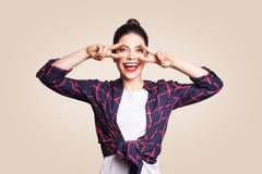 Победа и знак мира Счастливая зубастая молодая женщина smiley держа руку на глазах и показывая знак победы с удовлетворенной стор Стоковые Фото