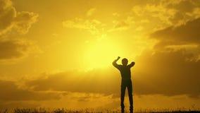 Победитель мальчика скачет верхняя часть на заход солнца