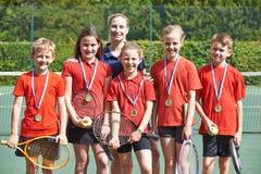Победоносная команда тенниса школы с медалями стоковые фотографии rf