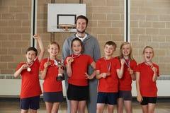 Победоносная спортивная команда школы с медалями и трофеем в спортзале стоковые изображения