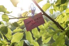 Побледнейте - украсьте дырочками покрашенный кусок бумаги держа день земли знака счастливый Стоковые Изображения RF