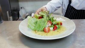 Повар дает законченный салат в кухне ресторана видеоматериал